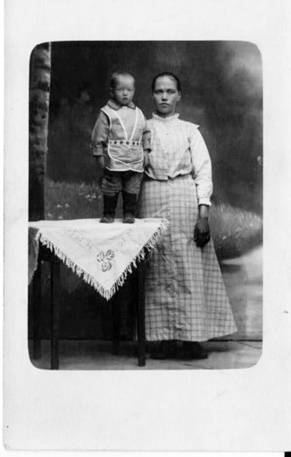Kuvassa pieni lapsi seisoo pöydällä ja nuori äiti vierellä